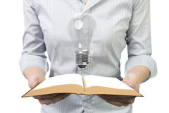 拿着与电灯泡的手开放书 免版税库存照片