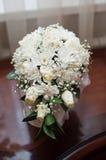 拿着与白玫瑰和其他花的新娘婚礼花束 免版税库存图片