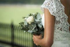 拿着与白玫瑰的新娘婚礼bouqet 免版税库存图片
