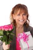 拿着与礼物的可爱的妇女桃红色玫瑰 免版税库存照片
