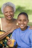 拿着与祖母的男孩橙汁  免版税图库摄影
