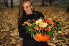 拿着与秋天的微笑的卖花人一个南瓜开花 免版税图库摄影