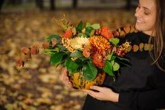 拿着与秋天的微笑的妇女一个南瓜开花 图库摄影