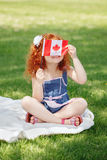 拿着与红槭叶子的逗人喜爱的矮小的红发白种人女孩孩子画象加拿大旗子,坐在公园outsi的草 免版税图库摄影
