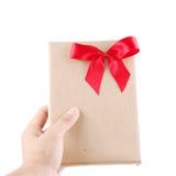 拿着与红色丝带的手葡萄酒礼物 免版税库存照片
