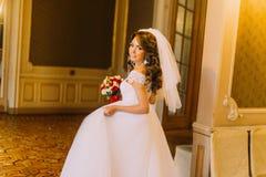 拿着与红色和白玫瑰的婚礼礼服的微笑的新娘逗人喜爱的花束看通过她的肩膀,当摆在时 库存图片