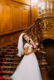 拿着与红色和白玫瑰的婚礼礼服的美丽的新娘逗人喜爱的花束摆在木葡萄酒的背景  免版税库存照片