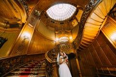 拿着与红色和白玫瑰的婚礼礼服的美丽的新娘逗人喜爱的花束摆在背景震惊 免版税库存图片