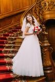 拿着与红色和白花的婚礼礼服的美丽的新娘逗人喜爱的花束摆在葡萄酒背景  免版税库存照片