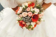 拿着与红色和白花的新娘婚礼花束 库存照片