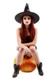 拿着与红色的一个迷人的红发巫婆的画象南瓜 免版税库存图片