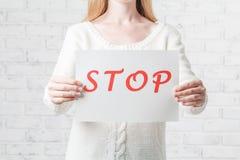 拿着与红色题字中止的女孩一个白色标志在w 免版税库存照片