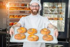 拿着与罂粟种子的一位年轻英俊的面包师新鲜的百吉卷在一个烤箱和一个机架的背景的一个盘子有焙烤食品的 库存图片