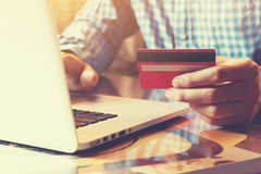 拿着与网上购物的年轻商人信用卡或 库存图片
