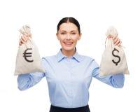 拿着与美元和欧元的女实业家袋子 免版税库存照片