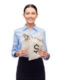 拿着与美元的女实业家金钱袋子 免版税库存图片