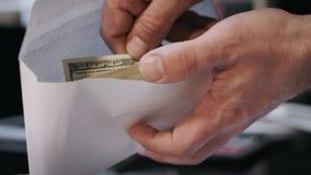 拿着与美元钞票的人信封 贿赂和腐败概念 股票录像