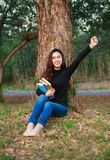 拿着与胳膊的快乐的妇女一本书在公园上升了 库存图片