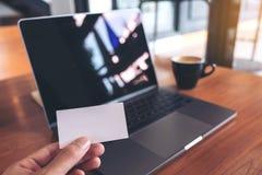 拿着与膝上型计算机和咖啡杯的手白色空的名片在木桌上 图库摄影