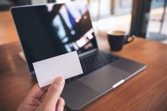 拿着与膝上型计算机和咖啡杯的手白色空的名片在木桌上 库存图片