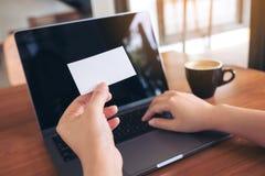 拿着与膝上型计算机和咖啡杯的手白色空的名片在木桌上 免版税库存照片