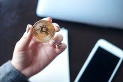 拿着与膝上型计算机和手机的女商人一金黄颜色bitcoin在桌上在办公室 免版税库存图片
