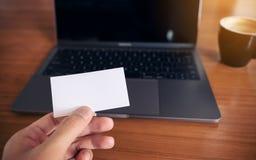 拿着与膝上型计算机的手白色空的名片在木桌上 库存照片