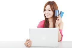 拿着与膝上型计算机的美丽的少妇信用卡 免版税图库摄影