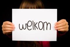 拿着与荷兰词韦尔科姆-欢迎的孩子标志 免版税库存照片