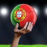 拿着与葡萄牙旗子的人足球 免版税库存图片