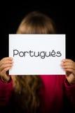 拿着与葡萄牙词Portugues -葡萄牙语的孩子标志我 免版税图库摄影