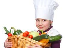 拿着与蔬菜的一点厨师一个篮子 免版税库存图片