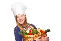 拿着与蔬菜的小辈厨师一个篮子 免版税库存图片