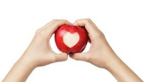 拿着与被雕刻的心脏的女性青少年的手苹果 免版税图库摄影