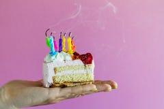 拿着与许多的女孩美丽的开胃生日蛋糕吹 图库摄影