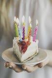 拿着与许多的女孩美丽的开胃生日蛋糕对光检查 免版税库存图片