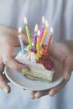 拿着与许多的女孩美丽的开胃生日蛋糕对光检查 免版税库存照片