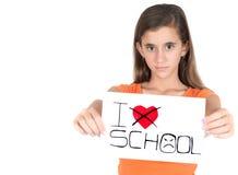 拿着与词的女孩一个标志我恨学校 免版税库存照片
