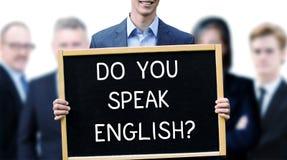 拿着与词的年轻商人一个标志您讲英语 库存照片