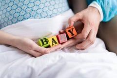 拿着与词婴孩的孕妇和医生五颜六色的立方体 库存图片