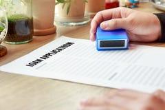 拿着与贷款的女商人一个批准的不加考虑表赞同的人applic 免版税库存照片