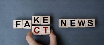 拿着与轻碰块伪造品的商人手木立方体对事实在桌背景的新闻词 新闻、解答和事务 库存照片