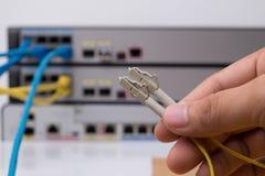 拿着与连接器的手视觉纤维缆绳 免版税图库摄影