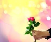 拿着与迷离的手红色玫瑰点燃bokeh 免版税库存图片
