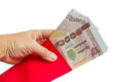 拿着与金钱的手红色信封。 库存图片