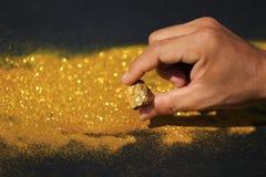 拿着与金黄光的人手纯净的金矿物在黑背景、投资和企业概念 免版税库存照片