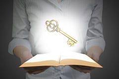 拿着与金黄欧洲标志的手开放书 免版税库存图片