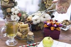 拿着与钳子、茶杯、苹果、礼物盒和花圈的手一个曲奇饼 库存照片