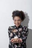 拿着与闪烁发光物的妇女一块杯形蛋糕 库存照片