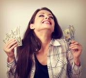 拿着与闭合的眼睛的笑的优胜者少妇美元  免版税库存照片